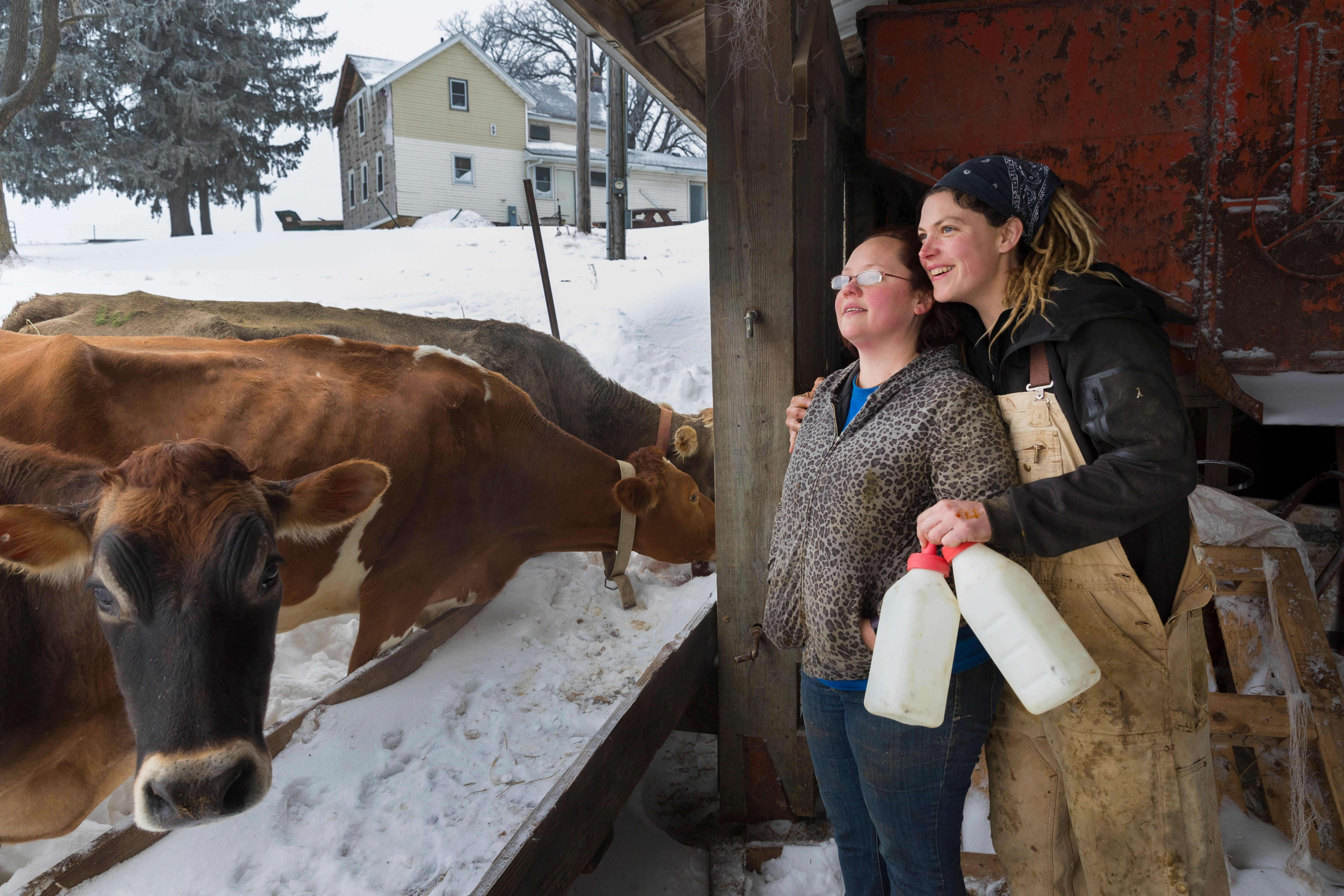 Brandi Harris (left) and her wife, Emily, check on their heifers on the dairy farm they own.