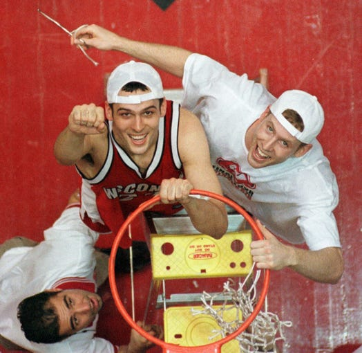 Wisconsin's Mike Kelley, center, and Jon Bryant, right, celebrate as they cut down the net after beating Purdue 64-60 in the NCAA West Regional in Albuquerque, N.M., Saturday, March 25, 2000.