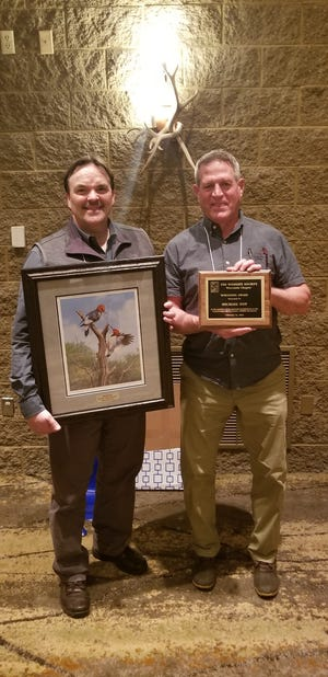Mike Foy (right), a retired DNR wildlife biologist who lives in Madison, is presented with the Wisconsin Award by Scott Hygnstrom, president of the Wisconsin chapter of The Wildlife Society.