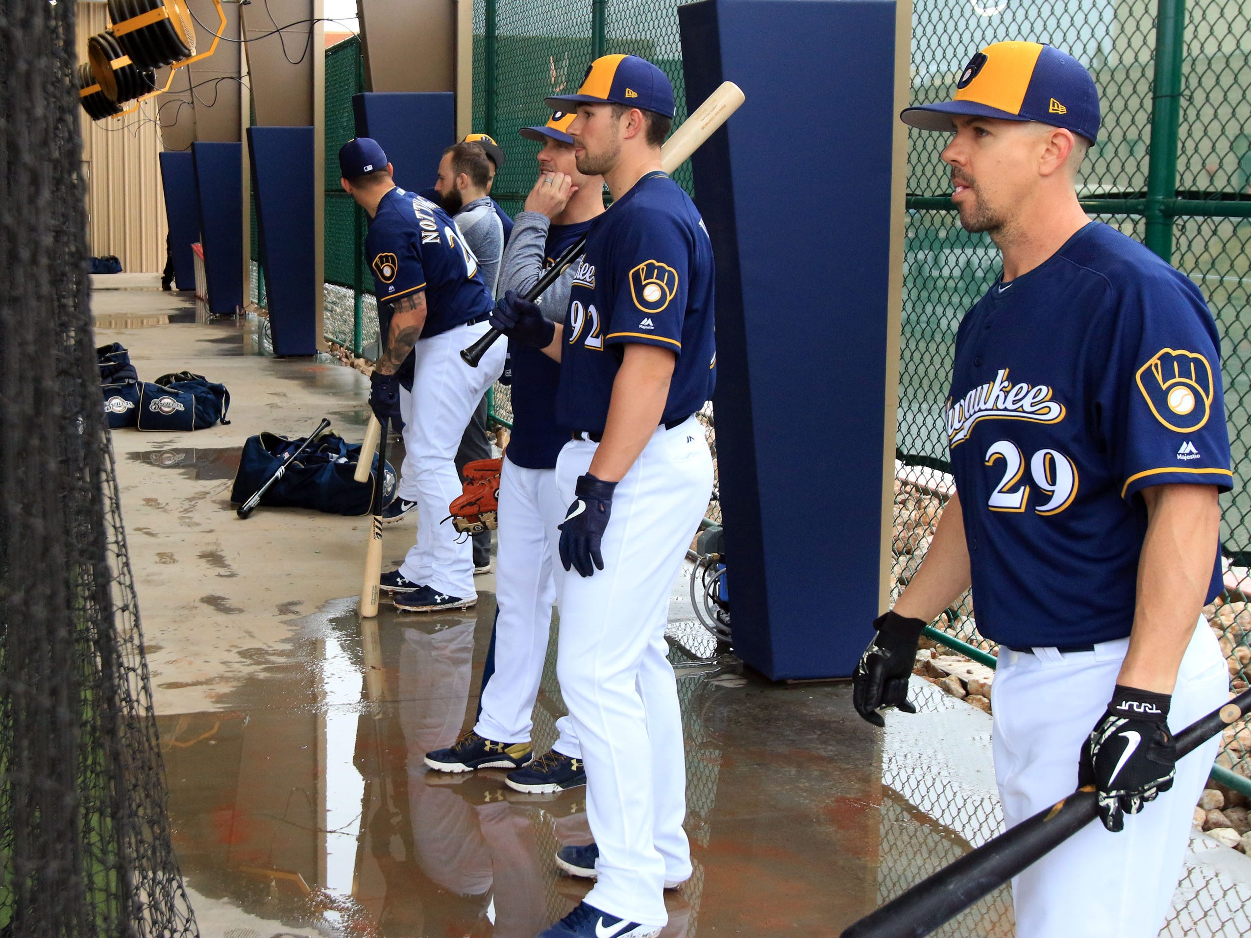 Players wait to get in their swings in the batting cages on a rainy Thursday in Phoenix.