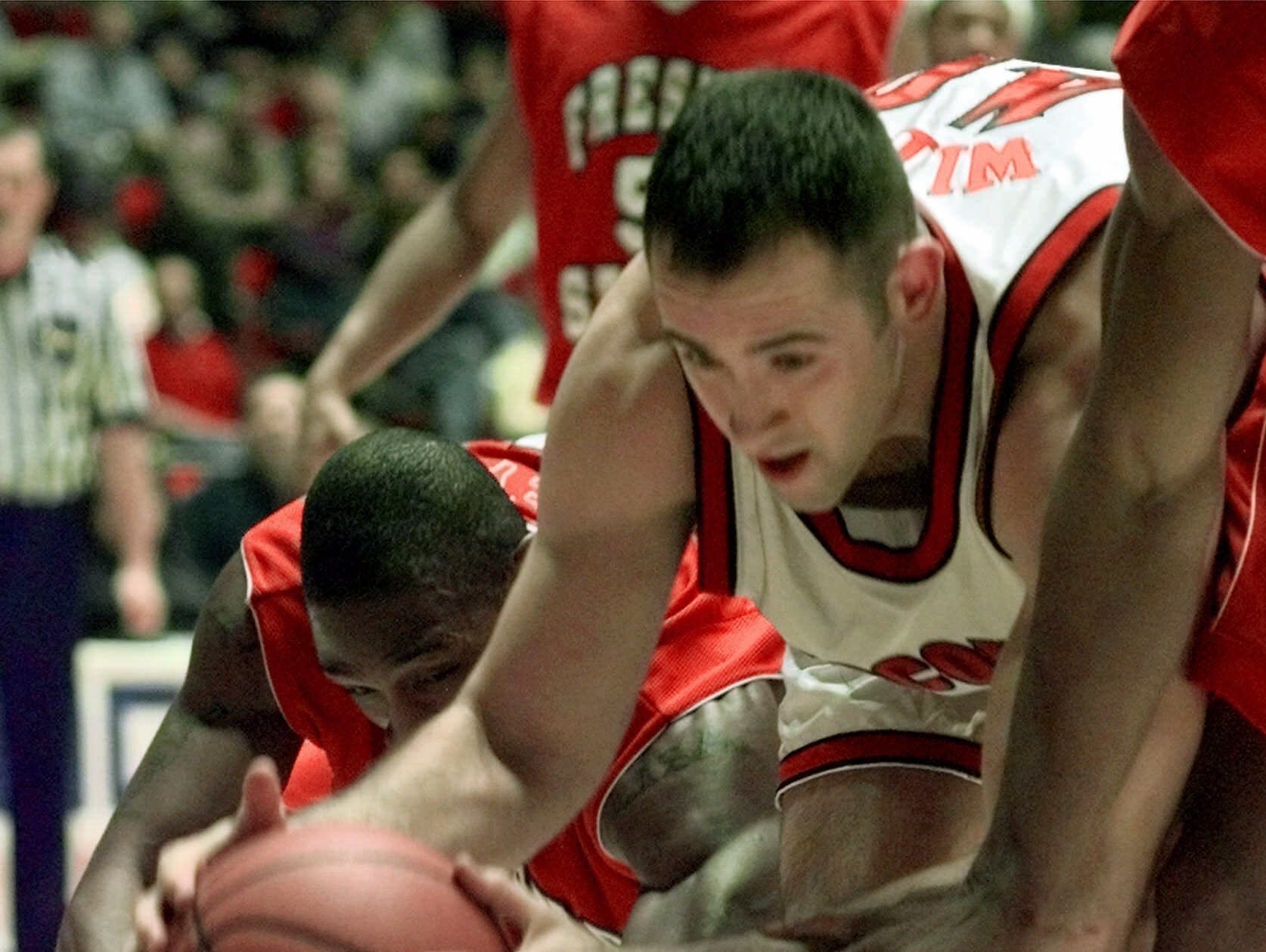 Wisconsin's Charlie Wills, right, comes in low past Fresno State's Larry Abney, left, to retrieve a loose ball in the first half of their first-round NCAA West Regional game in Salt Lake City, Thursday, March 16, 2000.