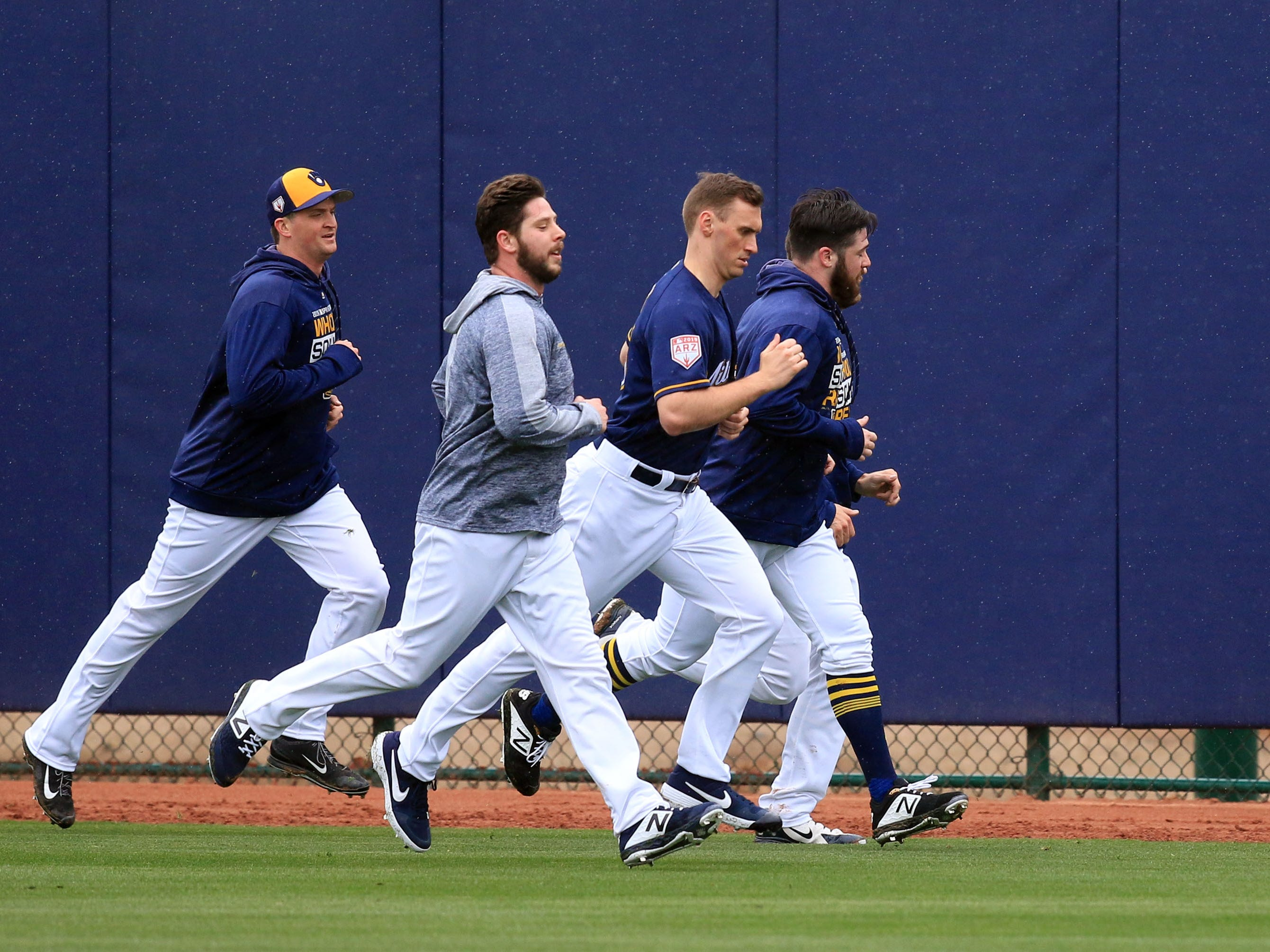 A group of pitchers dodge rain drops as they get in some running on Thursday.