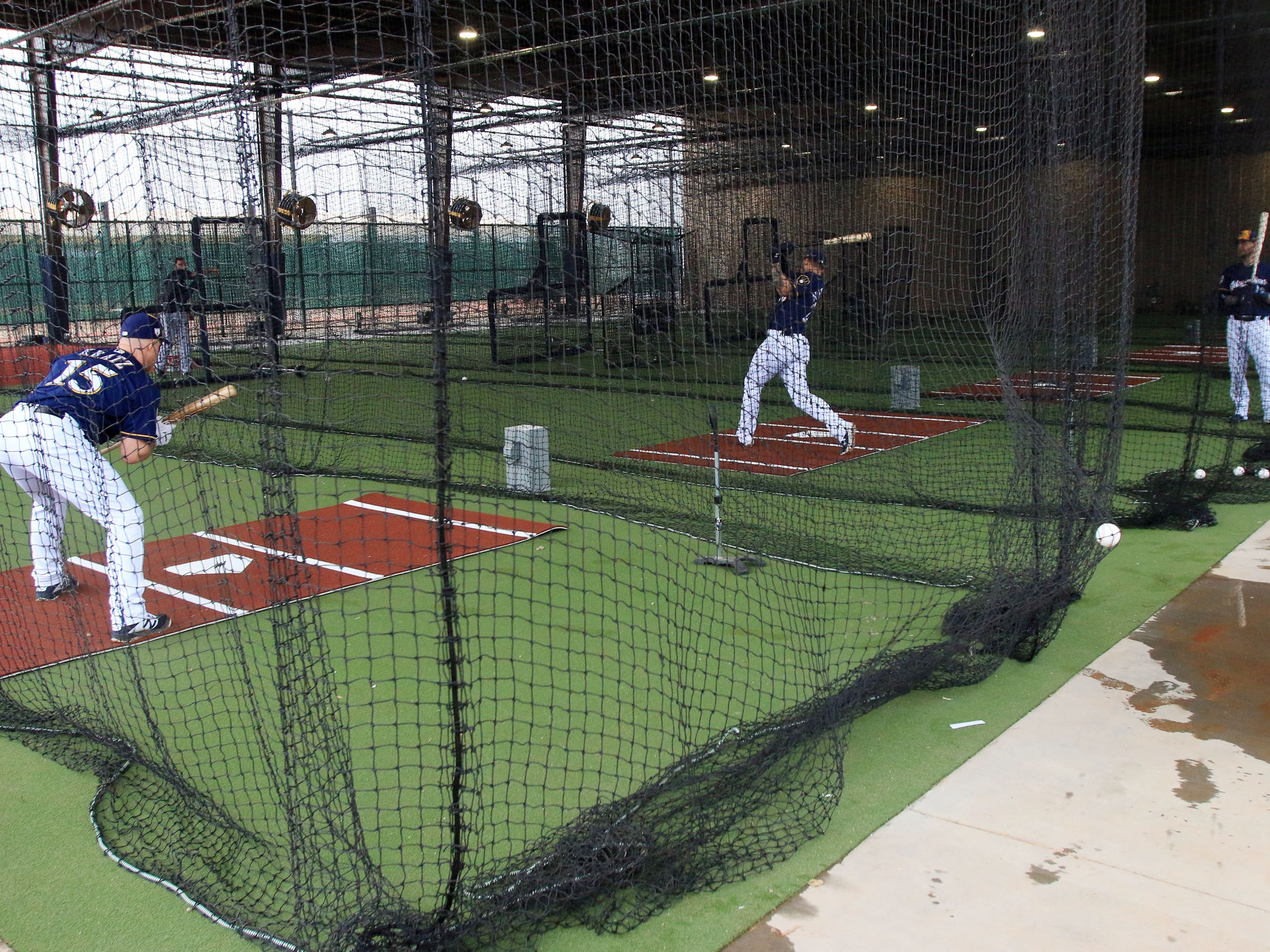 Brewers players get their cuts in using the team's  new covered batting cages at American Family Fields of Phoenix. Position players put them to  good use as a consistent rain soaked Phoenix on Thursday.