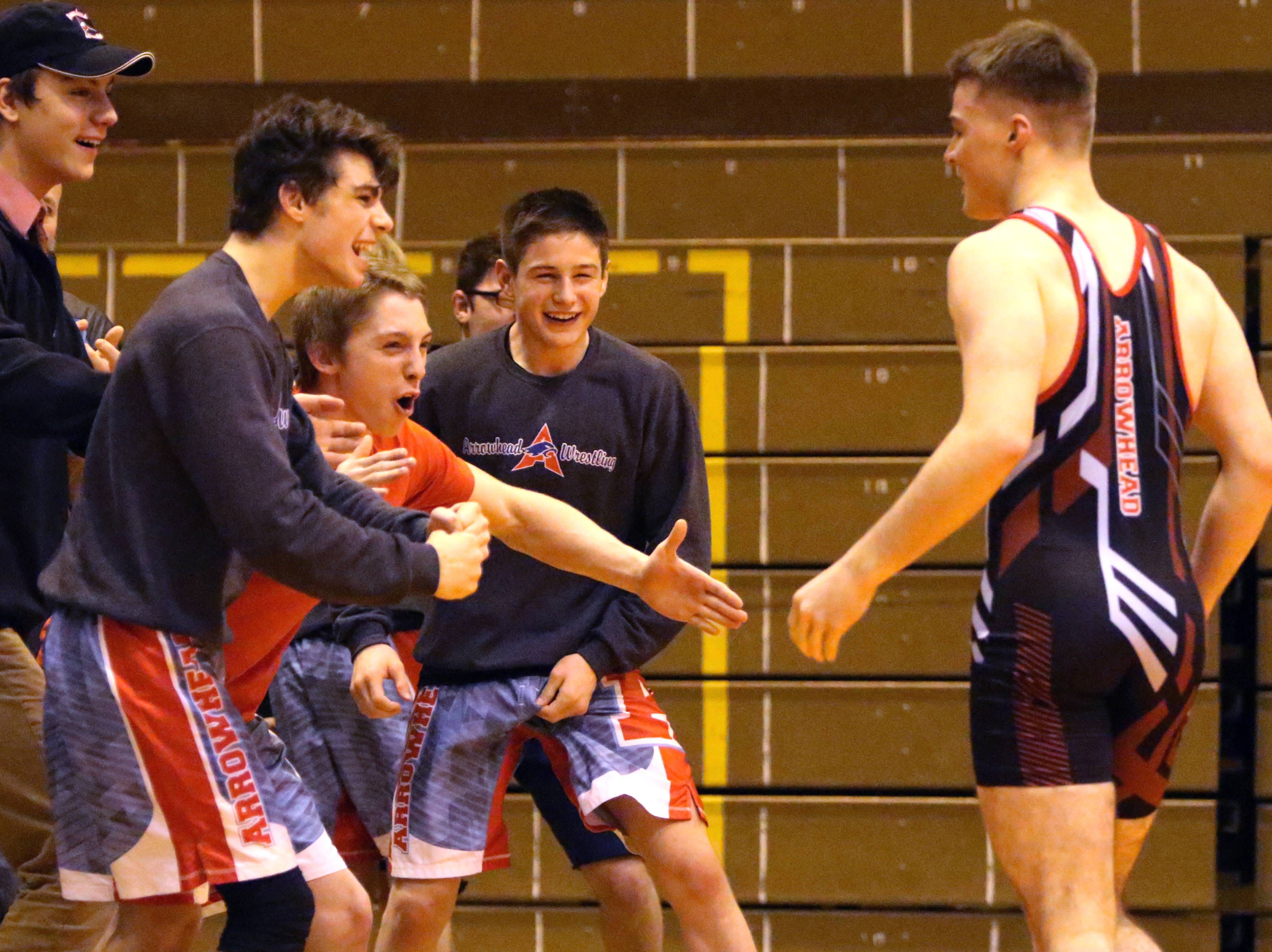 Arrowhead teammates congratulate Noah Ross (right) after his pin in the final match during a WIAA sectional final on Feb. 14, 2019 sent the Warhawks to the WIAA state team meet.