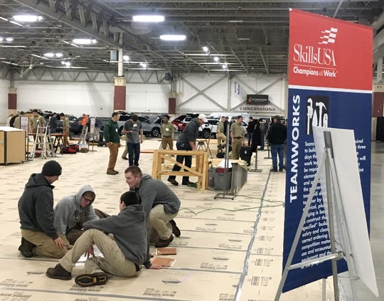 Four-member teams of high school students study their blueprint the day before the annual SkillsUSA Carpentry Teamworks competition at the Milwaukee NARI Spring Home Improvement Show.
