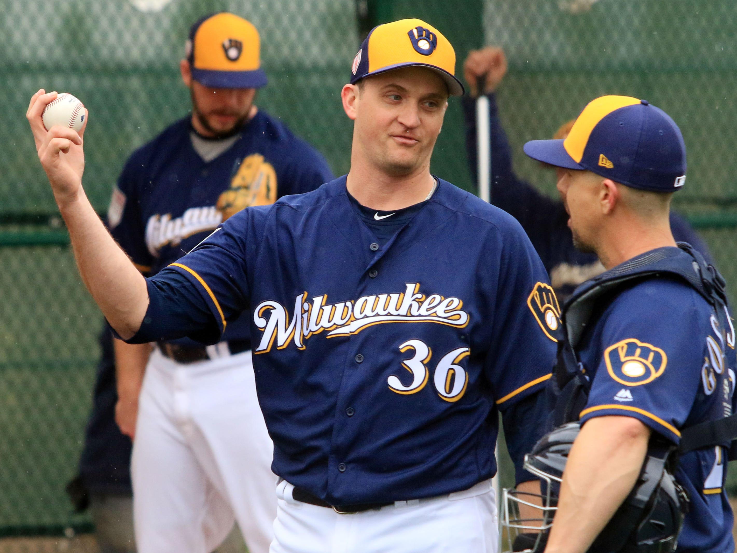 Brewers relief pitcher Jake Petricka  talks with catcher Tuffy Gosewisch, a non-roster invitee,  following a bullpen session on Thursday.
