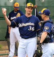 Brewers relief pitcher Jake Petricka talks with catcher Tuffy Gosewisch, a non-roster invitee, following a bullpen session.