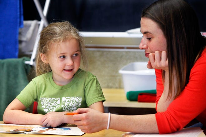 Highland Community School children's house assistant, Mary Claire Short, right, works with K-5 student Louisa Krey on a reading assignment on Thursday, Feb. 14, 2019.