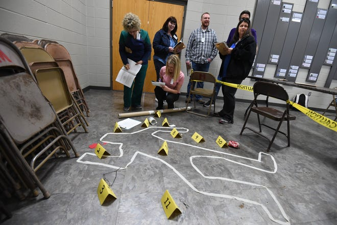 Nursing leaders from Baxter Regional Medical Center learn about crime scene investigation Friday during a team building event taught by Health and Human Science students at Mountain Home High School. To see a photo gallery taken during the event, go to www.baxterbulletin.com
