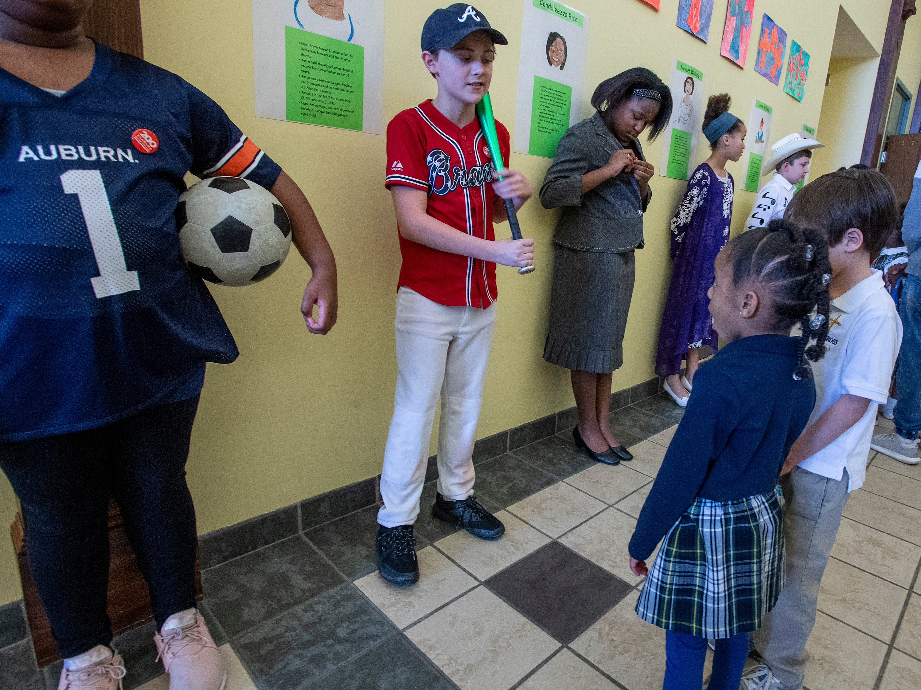 Young students hear about Hank Aaron from Ethan Scott as students portray Alabamians in their Alabama Bicentennial Wax Museum, telling the stories of their characters to visitors, at Holy Cross Episcopal School in Montgomery, Ala., on Friday February 15, 2019.
