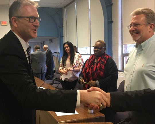 Chuck Reynolds shakes hands with Muncie School Board members after being hired Friday as associate superintendent.