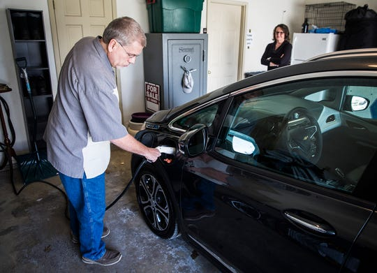 Rick Morris uses the charger he and his wife had installed in their garage for their electric car.