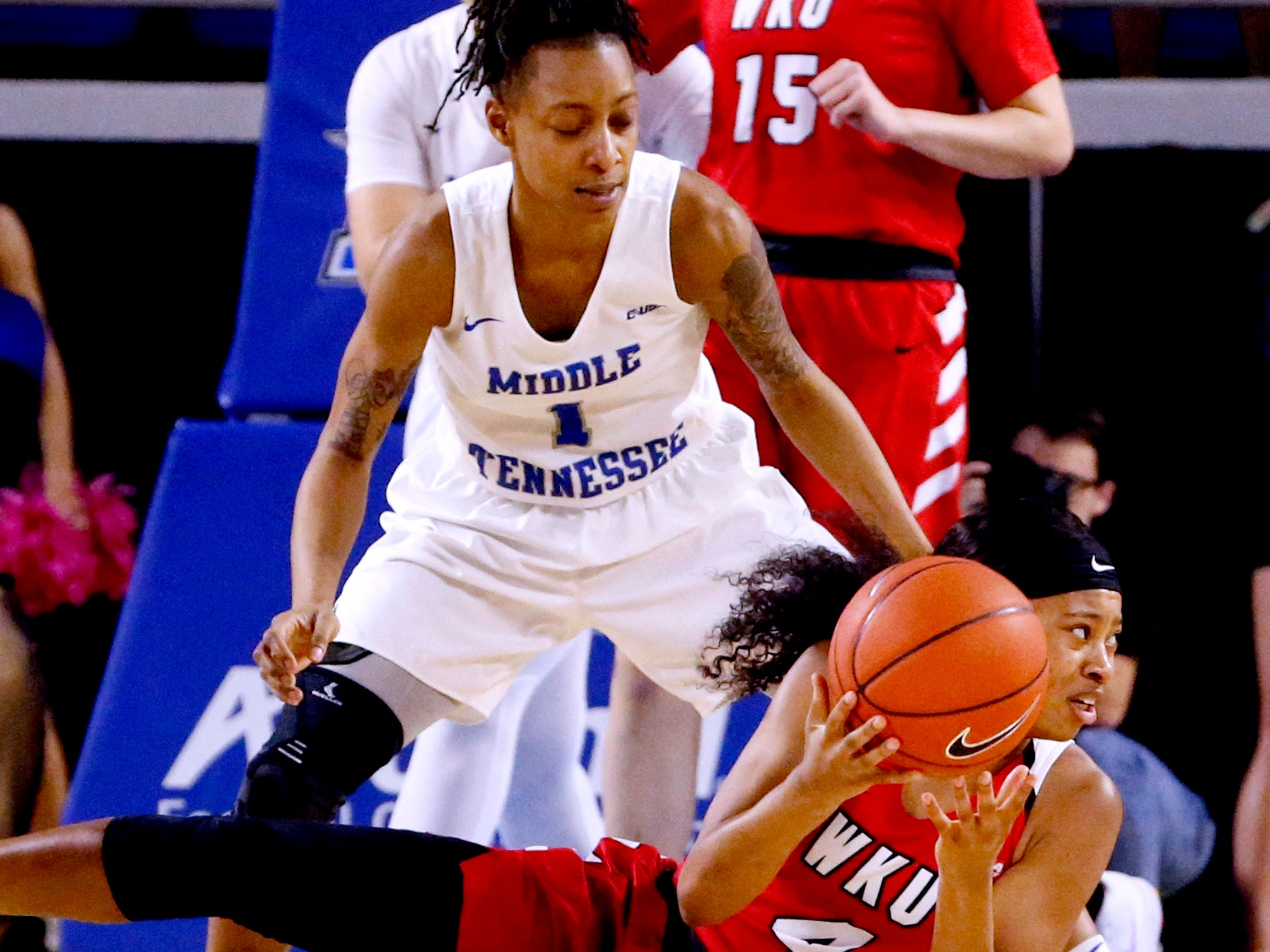Western's forward Dee Givens (4) galls to the floor with the ball as MTSU's guard A'Queen Hayes (1) guards her on Thursday, Feb. 14, 2019.