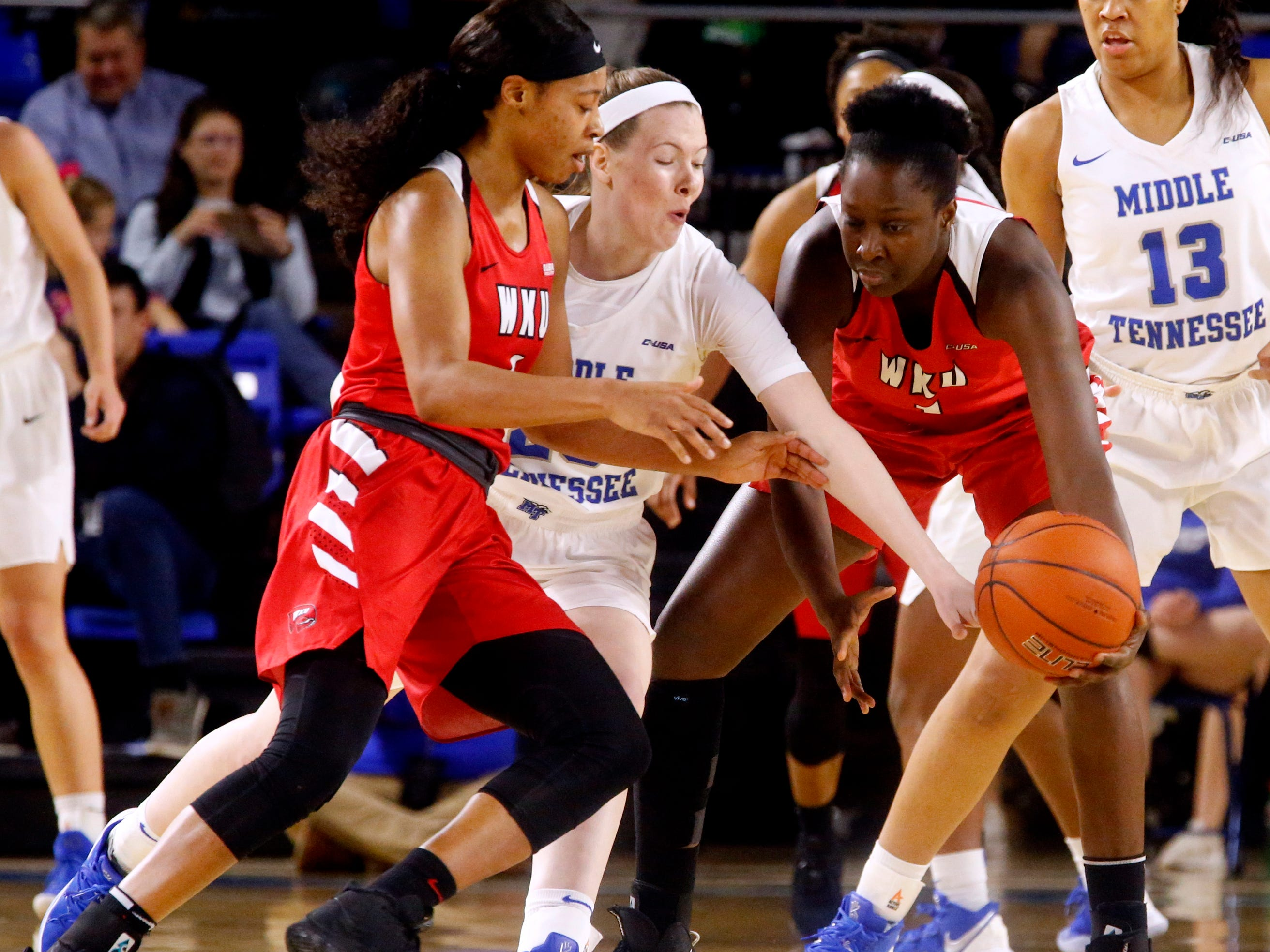 MTSU's guard Alexis Whittington (23) tries t get the ball away from Western's forward Dee Givens (4) and Western's forward Arame Niang (1) on Thursday, Feb. 14, 2019.