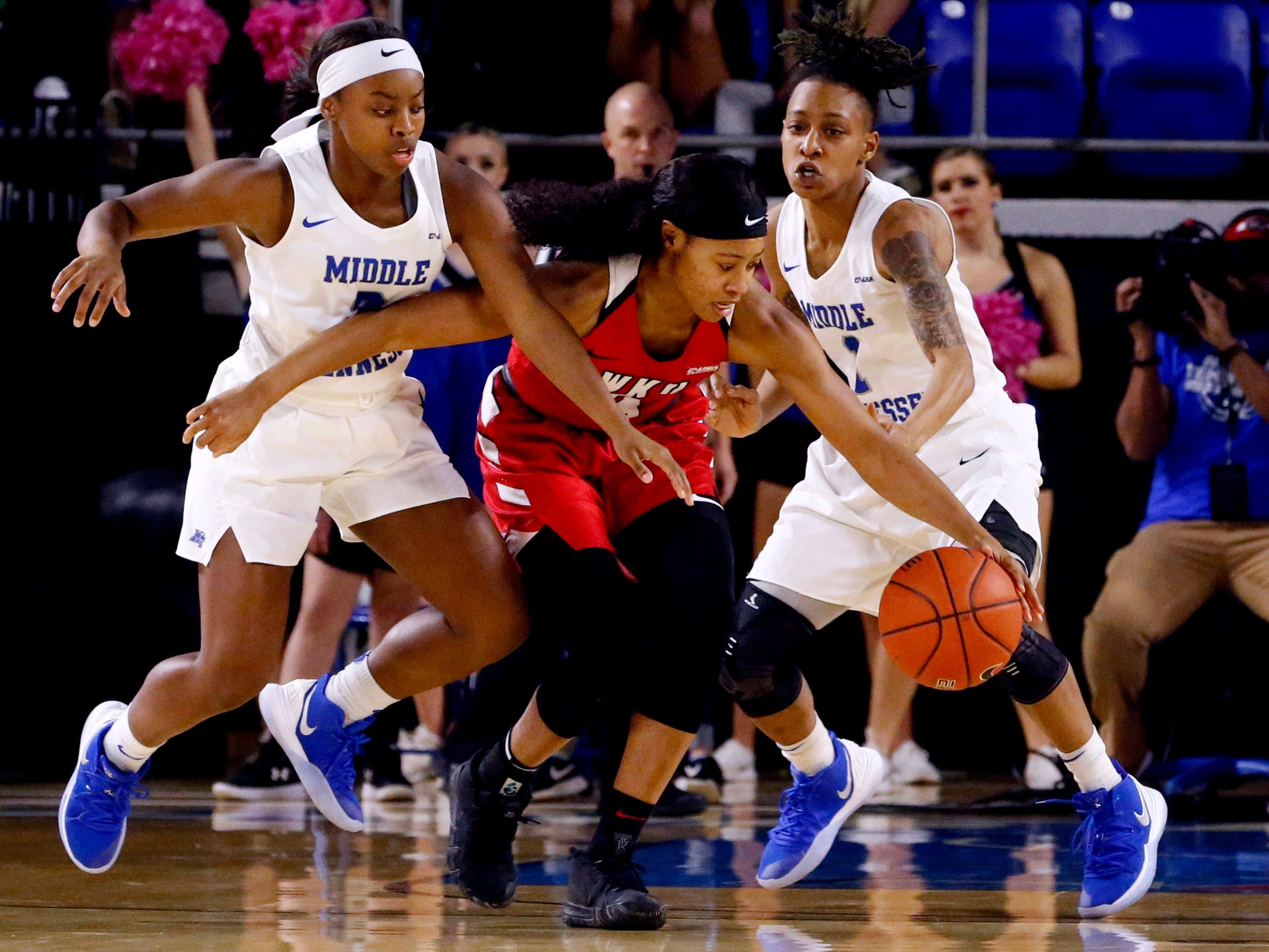 Western's forward Dee Givens (4) dribbles the ball as MTSU's guard Taylor Sutton (2) and MTSU's guard A'Queen Hayes (1) both try to steal the ball away on Thursday, Feb. 14, 2019.