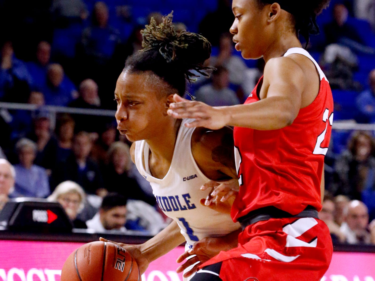 MTSU's guard A'Queen Hayes (1) moves the ball around the court as Western's guard Sherry Porter (22) guards her on Thursday, Feb. 14, 2019.