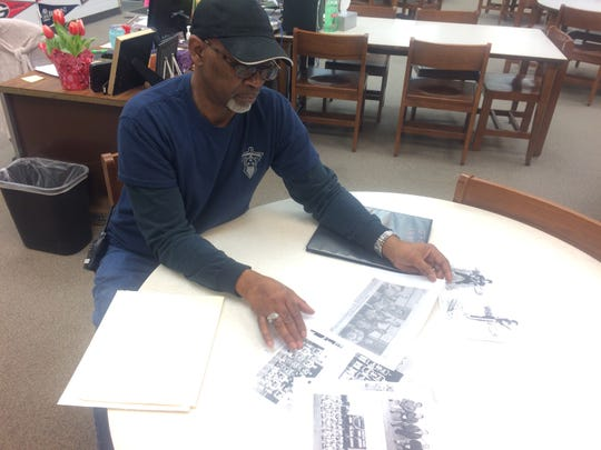 "Robert Rice looks through photocopies of Gallatin High School yearbook photos from the early 1970s in the school's library. Rice played basketball for the team when the school merged with Union High School in 1970-71. He said that's when it became ""the real Gallatin High."""