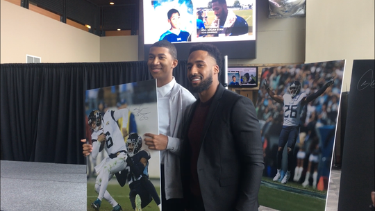 Brett Harris, 17, of Chicago, poses with Tennessee Titans cornerback Logan Ryan after winning a poster signed by the latter during an event as part of the Nissan Resume Challenge with 100 Black Men of America at Nashville's Nissan Stadium.