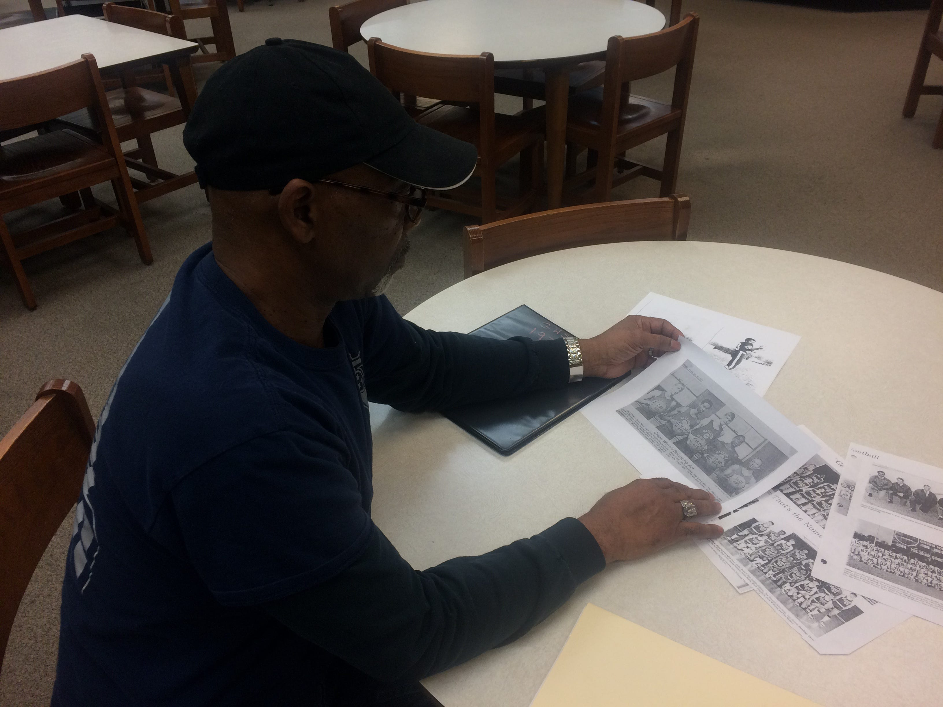 """Robert Rice looks through photocopies of Gallatin High School yearbook photos from the early 1970s in the school's library. Rice played basketball for the team when the school merged with Union High School in 1970-71. He said that's when it became """"the real Gallatin High."""""""