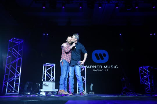 Blake Shelton kisses Dierks Bentley upon receiving his CRS Artist Humanitarian Award.