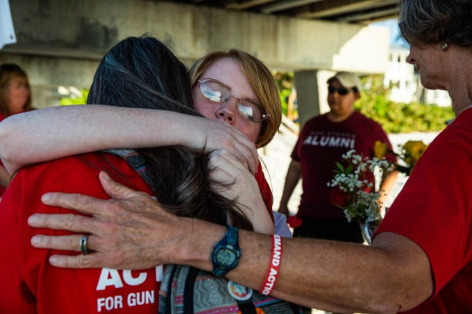 Student organizer Michaela O'Brien comforts Tina Ottman, a former teacher at Marjory Stoneman Douglas High School, at a vigil held in remembrance of the 17 lives lost in the Parkland mass shooting one year ago, held at Naples Pier on February 14, 2019.