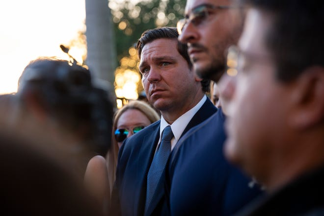Governor Ron DeSantis listens to speakers during an interfaith vigil at Pine Trails Park in Parkland, Florida, on Thursday, February 14, 2019.