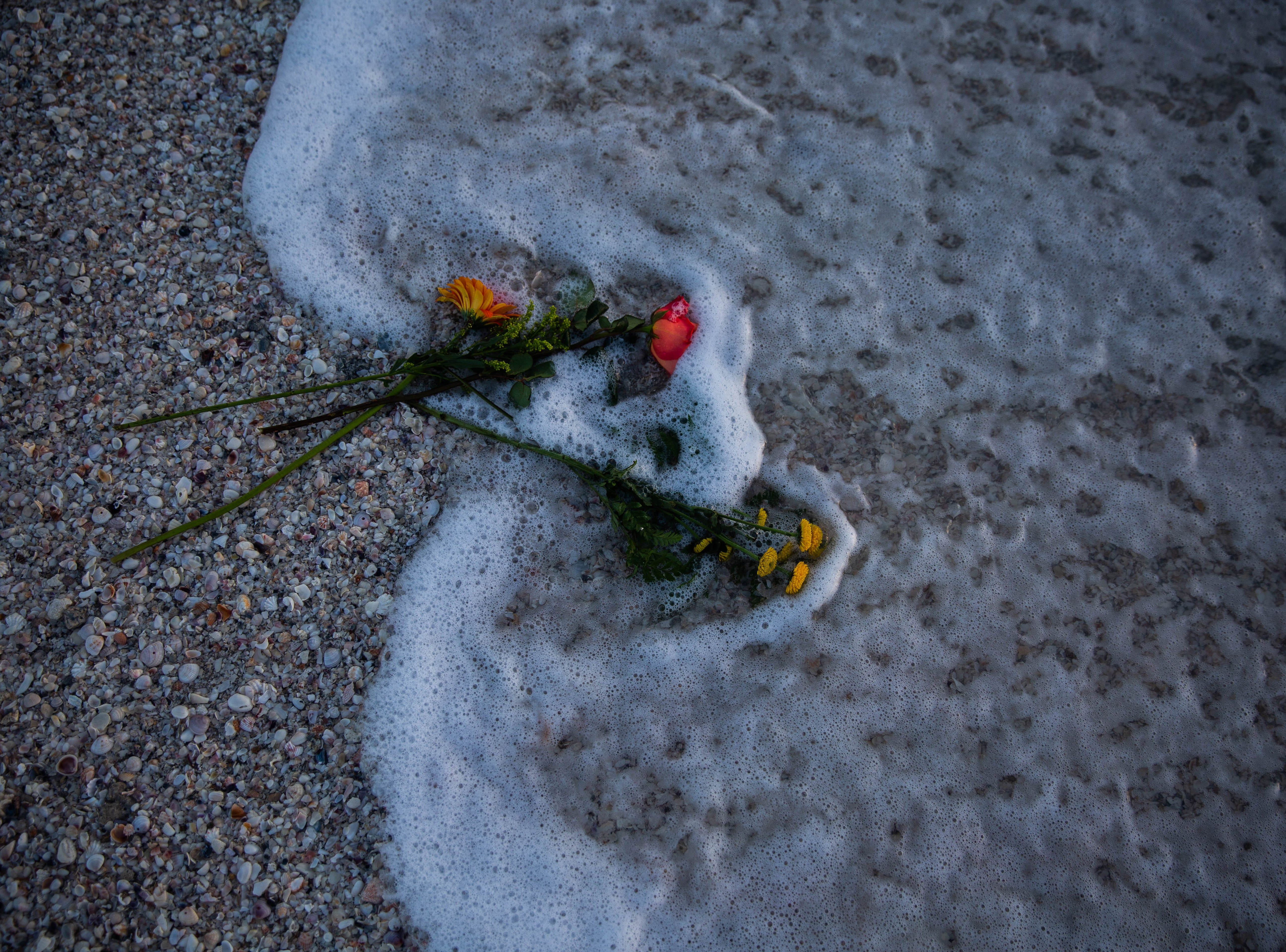 Flowers were tossed in the ocean at a vigil held at Naples Pier in remembrance of the mass shooting in Parkland one year ago.