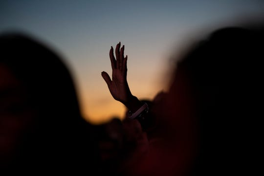 Cynthia Johnson of West Palm Beach waves her hand in the air during a closing song during an interfaith vigil at Pine Trails Park in Parkland, Florida, on Thursday, February 14, 2019.
