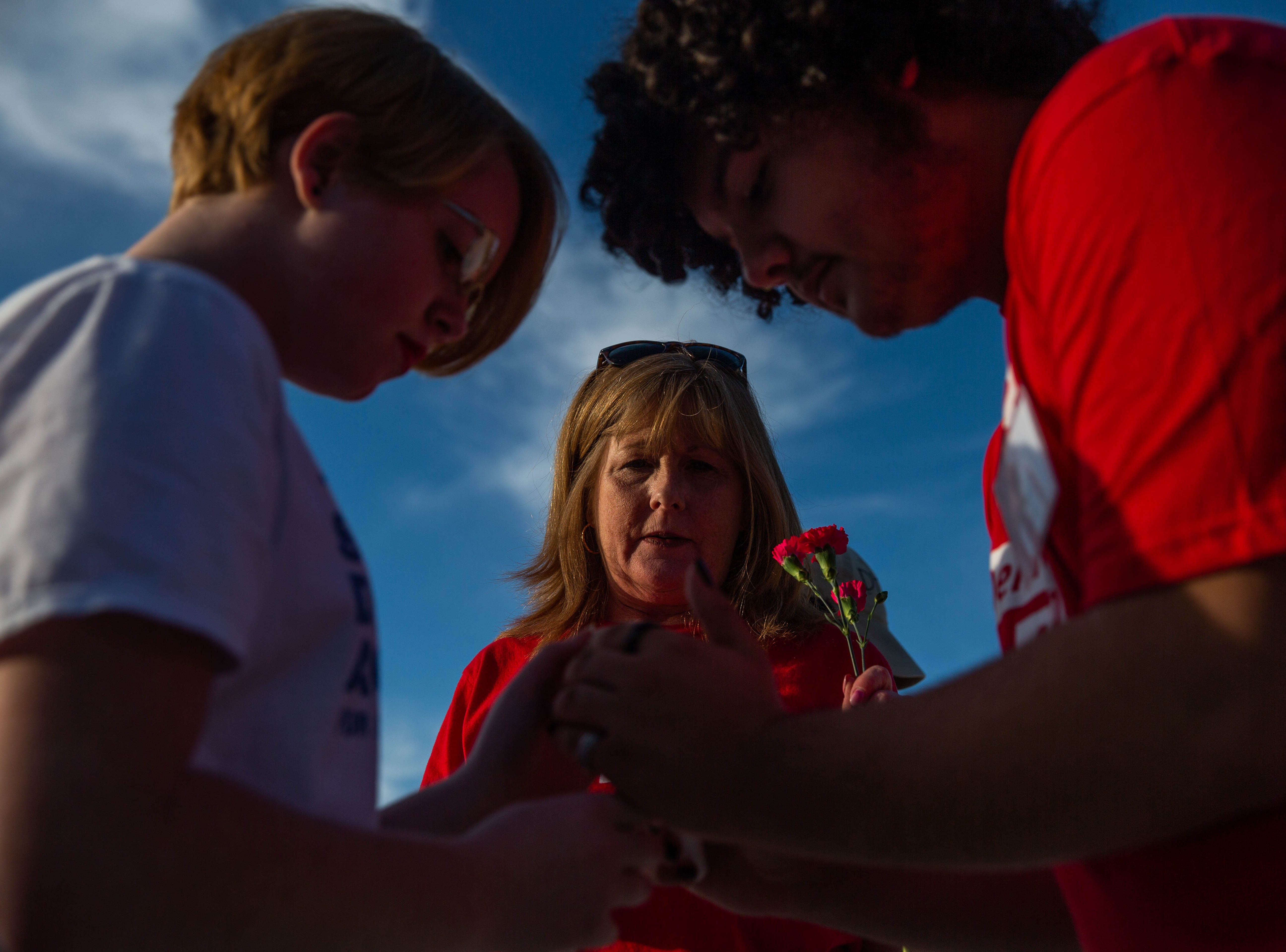 Kathy O'Brien watches as her daughter Michaela O'Brien and student Zac Vega light their candles at a student-organized vigil at Naples Pier on February 14, 2019. The vigil was in remembrance of the 17 lives lost in Parkland one year ago.