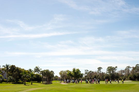 People traverse across the fairway of a hole during the first round of the Chubb Classic in The Classics at Lely Resort on Friday.