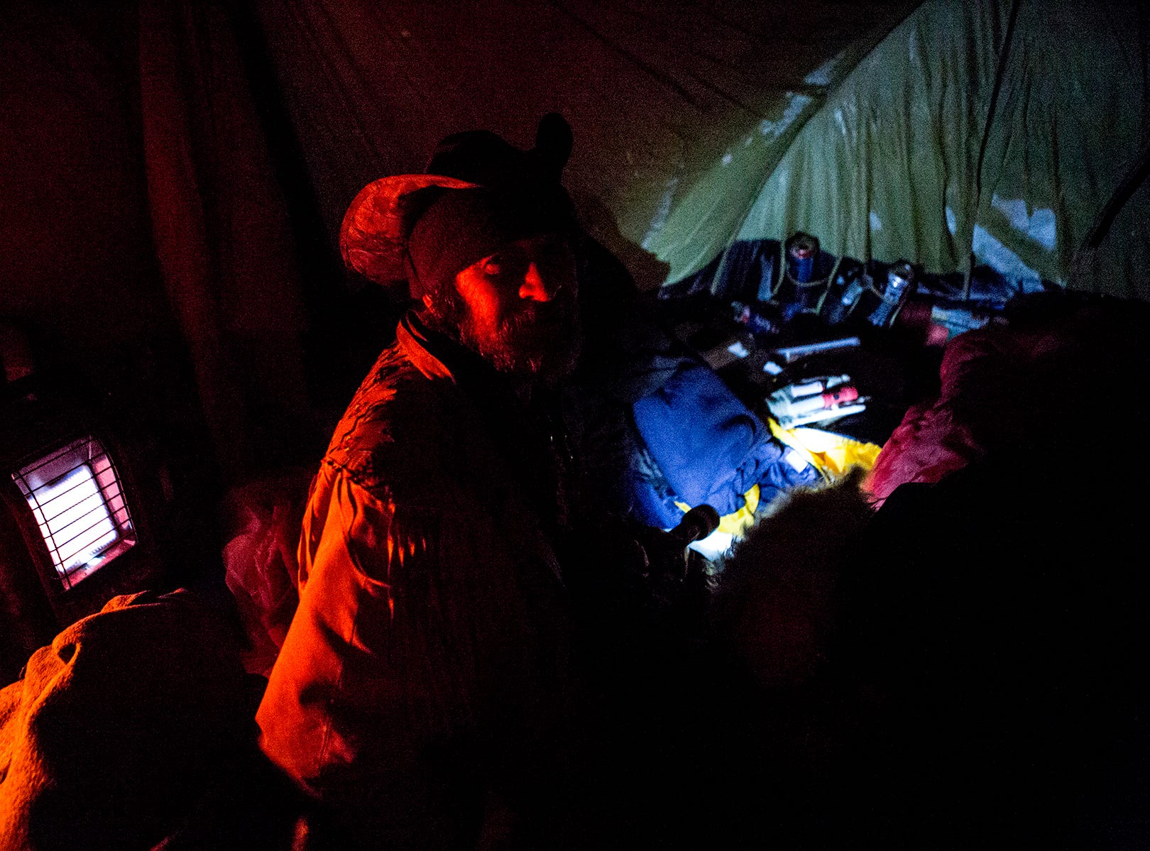 Cowboy in the tent he shares with three other men and their dogs, Jan. 30, 2019. Temperatures were below 0 but they all refused to go into warming shelters because they did not want to leave their dogs behind. Instead they hunkered down with sleeping bags and a propane heater running all night to survive the cold.