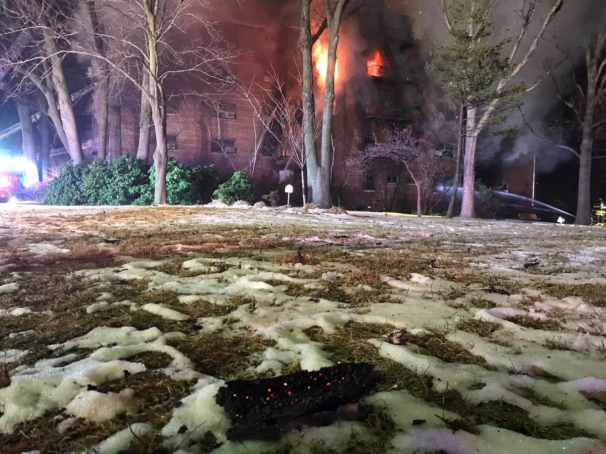 Debris lands on snowy grass from the large fire at an apartment building in Fort Lee on Thursday, Feb. 14, 2019.