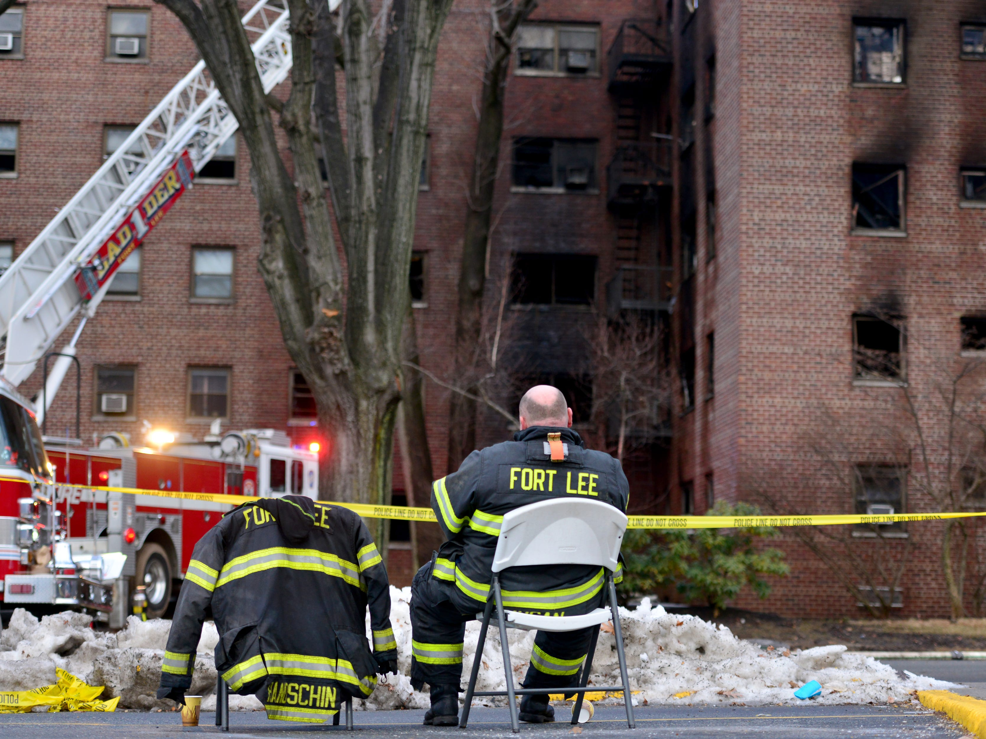 Fort Lee firefighter John Nugan closes his eyes after being at the fire scene since yesterday afternoon. Firefighters are hitting hot spots the morning after a fire broke out at an apartment complex on Edwin Ave in Fort Lee on Friday February 15, 2019.