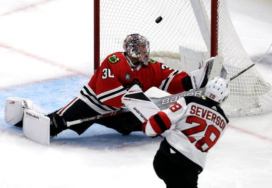 Chicago Blackhawks goalie Cam Ward, left, cannot stop a goal by New Jersey Devils defenseman Damon Severson, right, during the first period of an NHL hockey game Thursday, Feb. 14, 2019, in Chicago.