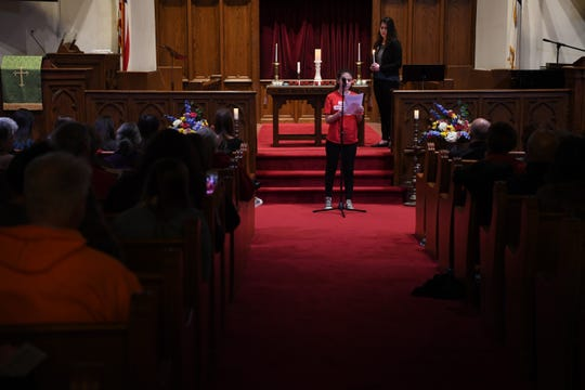 (center) Casey Bedwell-Coll reads the name of a student who was killed in a school shooting last year at Marjory Stoneman Douglas high school in Parkland, Florida, during a vigil at Emmanuel Baptist Church in Ridgewood on Thursday, February 14. (right) Sarah Emily Baum, co-founder of March For Our Lives NJ, holds a candle.