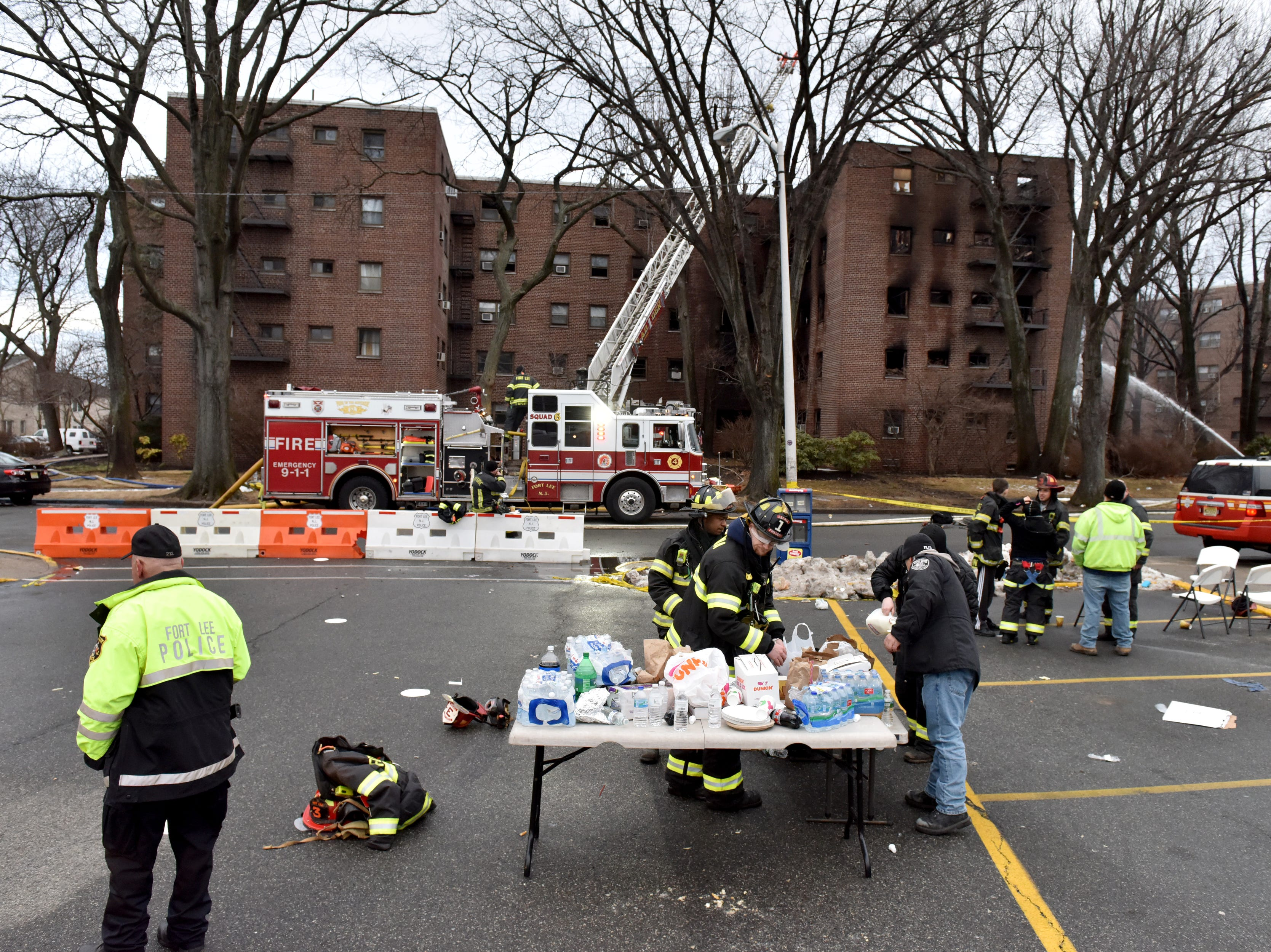 Firefighters eat breakfast at the fire scene while hitting hot spots the morning after a fire broke out at an apartment complex on Edwin Ave in Fort Lee on Friday February 15, 2019.