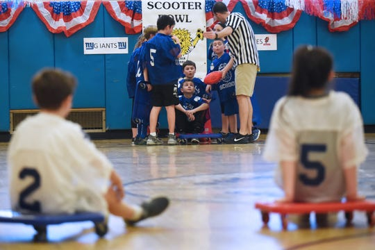 Wyckoff celebrates 25 years of Scooter Bowl, its indoor winter sport for fourth and fifth graders at Lincoln School in Wyckoff on Friday February 15, 2019. The referee talks with the Giants (blue) while the Buckeyes (white) wait on the court.