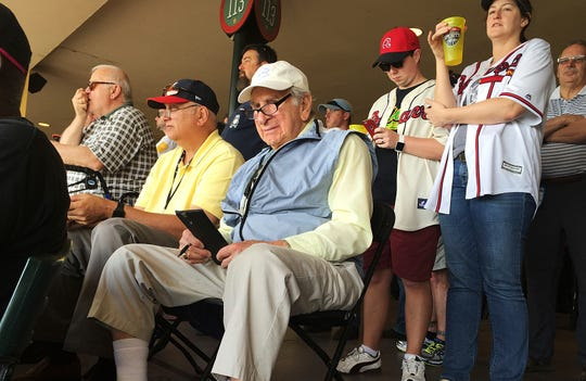 In this March 5, 2016, file photo, Tommy Giordano, special assistant to the general manager of the Atlanta Braves, scouts a spring training baseball game between the Braves and the Pittsburgh Pirates, in Kissimmee, Fla.  Giordano died Thursday, Feb. 14, 2019 at age 93.