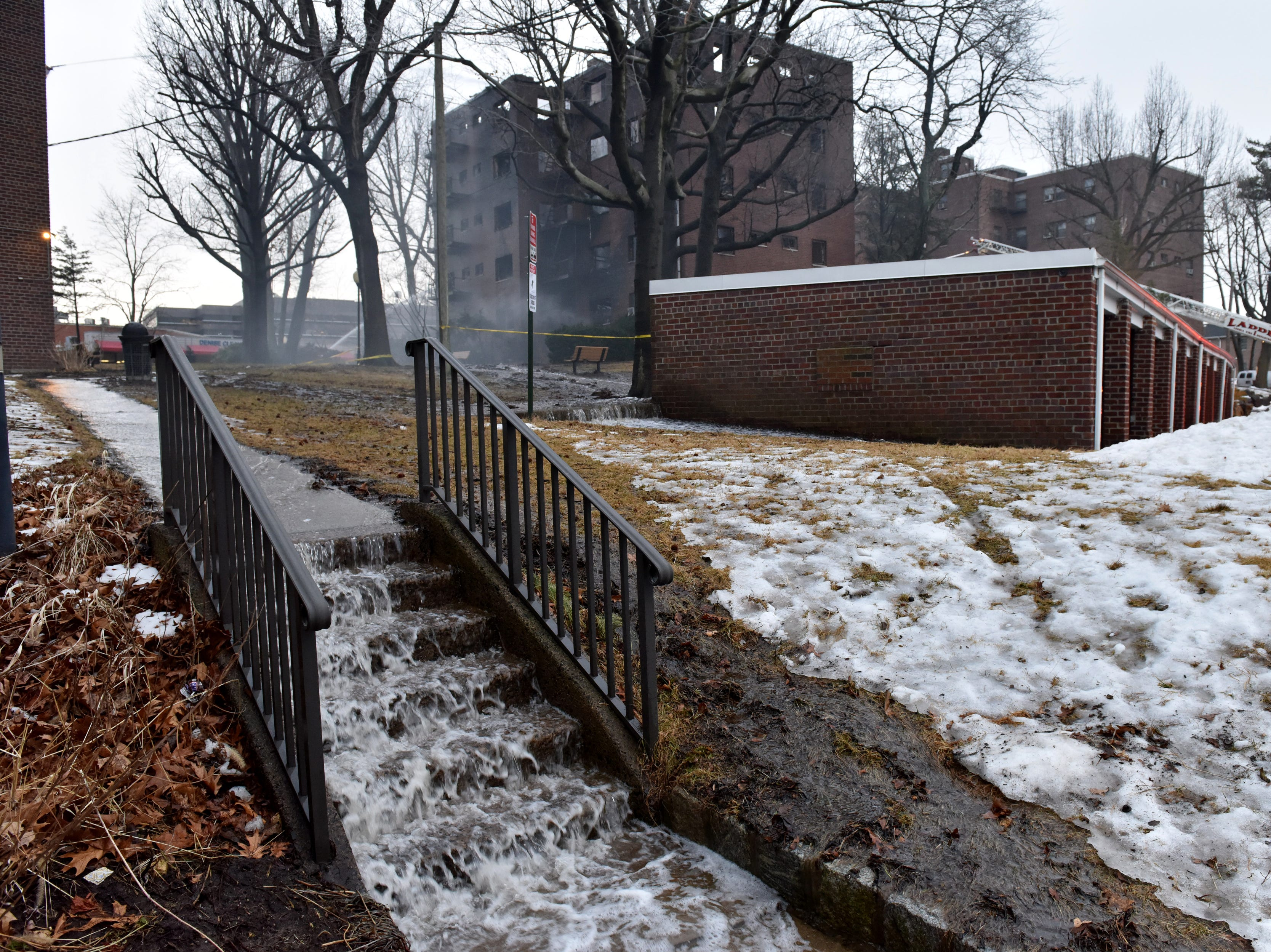 Water gushes down steps as firefighters are hitting hot spots the morning after a fire broke out at an apartment complex on Edwin Ave in Fort Lee on Friday February 15, 2019.