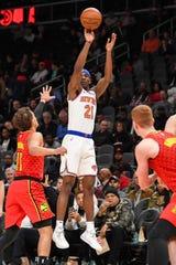 Feb 14, 2019; Atlanta, GA, USA; New York Knicks guard Damyean Dotson (21) shoots over Atlanta Hawks guard Trae Young (11) during the first half at State Farm Arena.