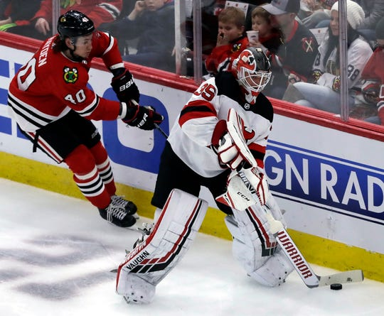 New Jersey Devils goalie Cory Schneider, right, looks to pass against Chicago Blackhawks right wing John Hayden during the second period of an NHL hockey game Thursday, Feb. 14, 2019, in Chicago.