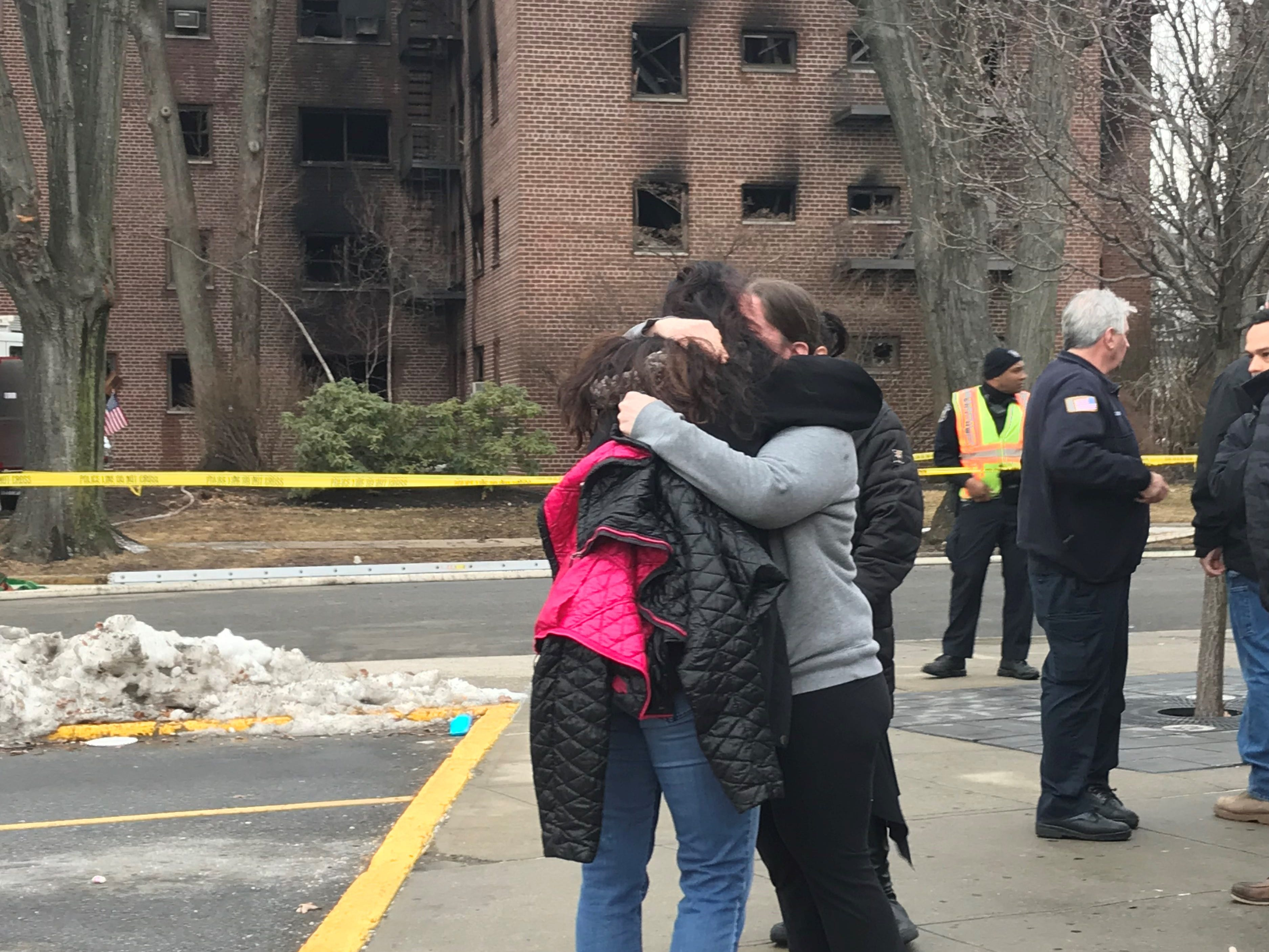 Megan Gaul, a resident of the Linwood Park building that caught fire in Fort Lee, shares an embrace after being told by firefighters that her cat Elijah was found alive.