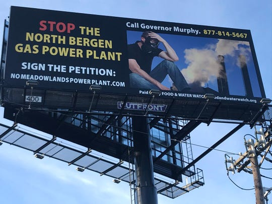 A billboard along the New Jersey Turnpike urging Gov. Phil Murphy to reject a proposed gas-fired power plant in the Meadowlands.