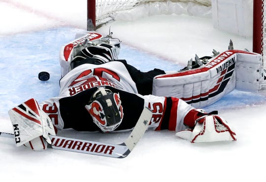 New Jersey Devils goalie Cory Schneider cannot stop a goal by Chicago Blackhawks center Jonathan Toews during the second period of an NHL hockey game Thursday, Feb. 14, 2019, in Chicago.