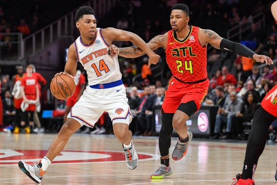 Feb 14, 2019; Atlanta, GA, USA; New York Knicks guard Allonzo Trier (14) dribbles against  Atlanta Hawks guard Kent Bazemore (24) during the first half at State Farm Arena.