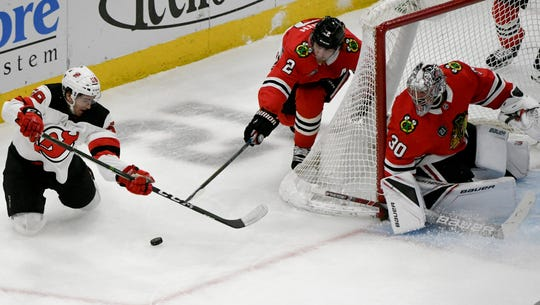 Feb 14, 2019; Chicago, IL, USA; New Jersey Devils center Kevin Rooney (58) shoots the puck as Chicago Blackhawks defenseman Duncan Keith (2) and Chicago Blackhawks goaltender Cam Ward (30) defend during the second period at the United Center.