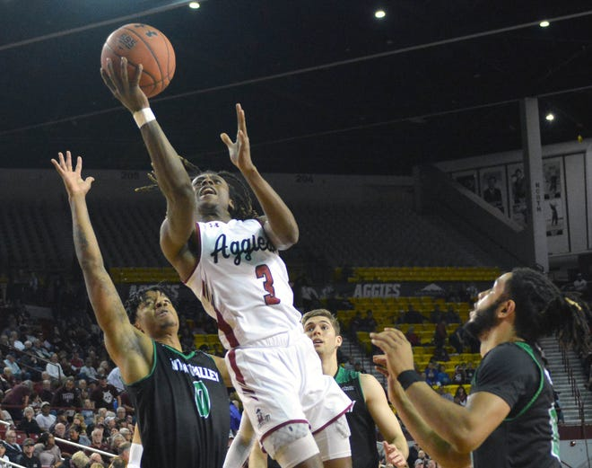 New Mexico State's Terrell Brown splits two Utah Valley defenders as he goes up for a layup during Thursday night's game at the Pan American Center.