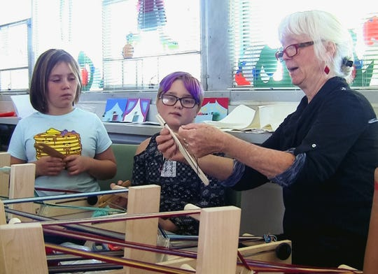 Collet Park students Presli Binkley and Kjeirsten Bell watch volunteer Gudrun Maunter demonstrate how to load a shuttle for weaving during a 4-H club meeting at Collet Park Elementary School.