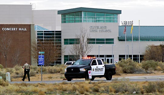 A Sandoval County Sheriff's Department deputy stands in front of Cleveland High School following a shots fired call in Rio Rancho, N.M., Thursday, Feb. 14, 2019. A shot was fired Thursday on the grounds of the suburban Albuquerque high school on the anniversary of the Parkland, Florida, high school massacre, but police and school officials said no one was injured and a suspect was in custody.