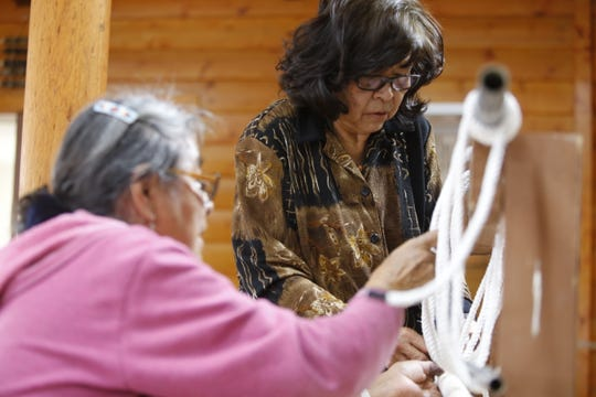 From left, Lois Becenti and Lisa Hudson situate a rod as part of the process to assemble a weaving loom during the Crownpoint Spin Off at Navajo Technical University on Friday.